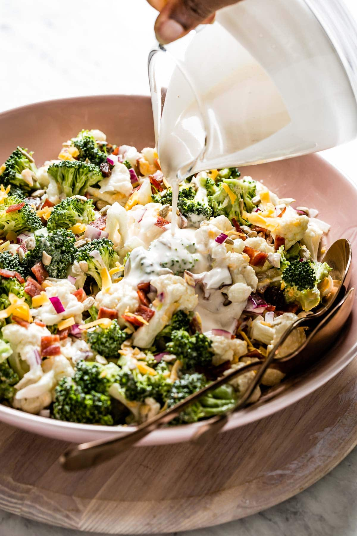 Person drizzling broccoli salad with bacon with dressing