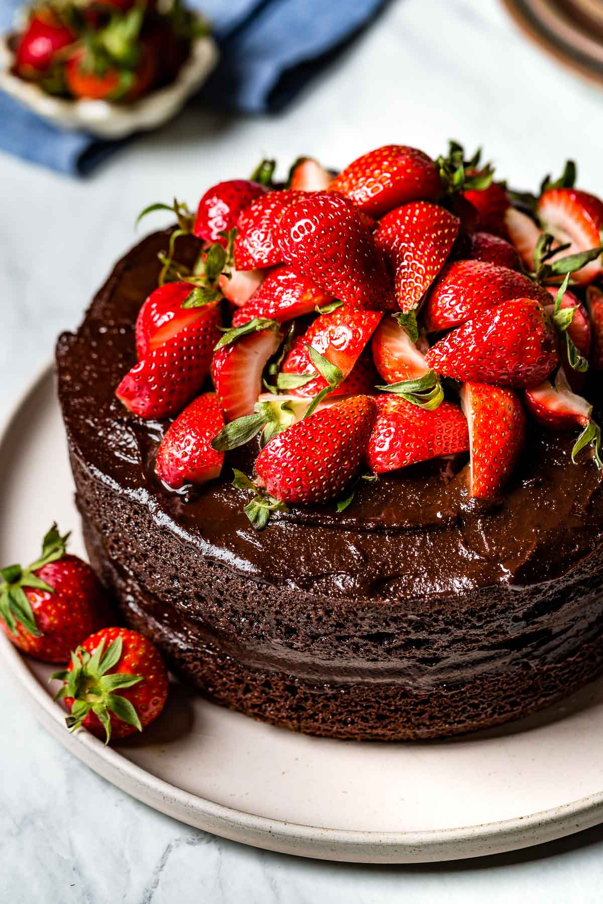 Almond Flour Chocolate Cake topped off with strawberries on a plate