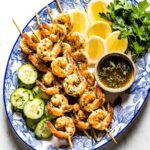 grilled shrimp on skewers on a plate with lemon slices, herbs, and cucumber slices