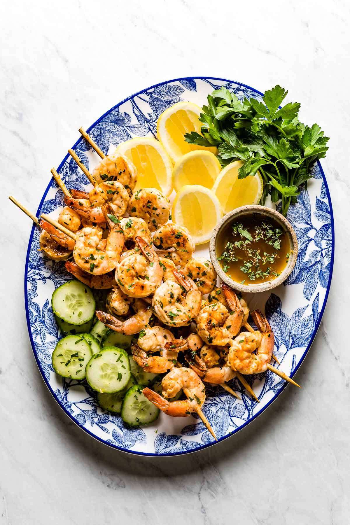 Grilled shrimp skewers on a plate with lemon, herbs and cucumber slices