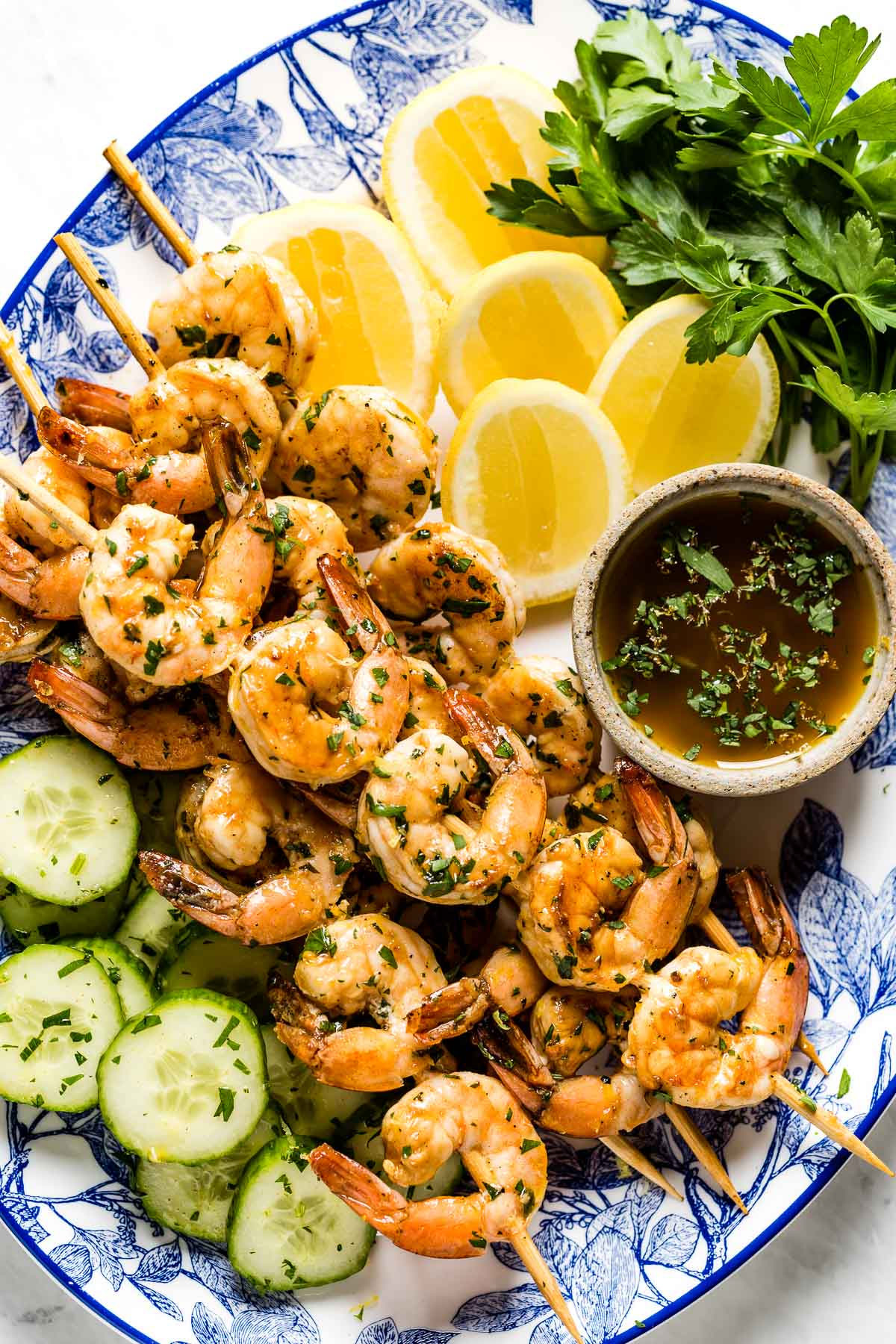 Grilled Shrimp Skewers on a plate with lemon slices, fresh parsley and cucumber slices