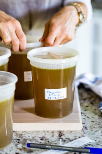 Ina Garten's Chicken Stock in a container with a person in the background