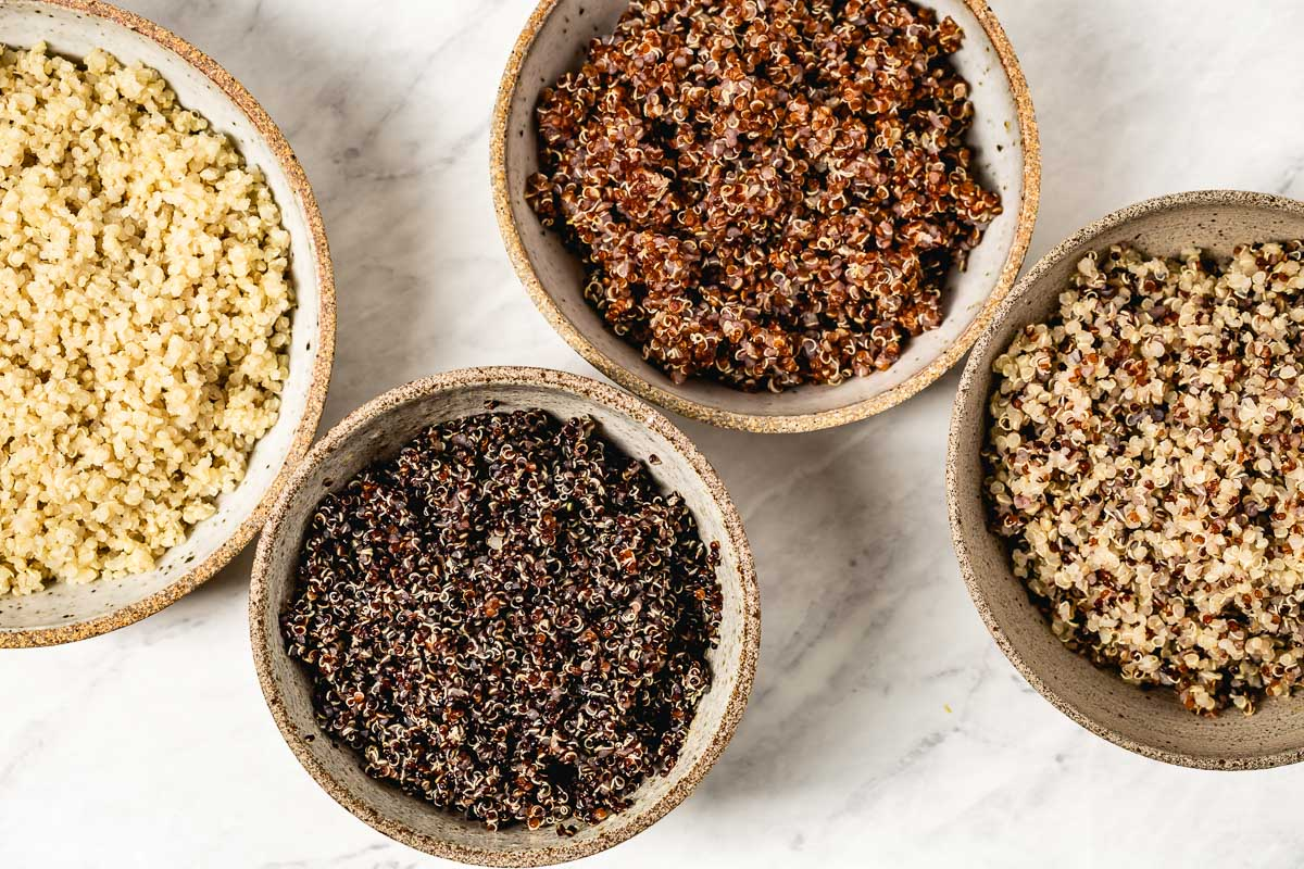 Four cooked quinoa types are in bowls from top view
