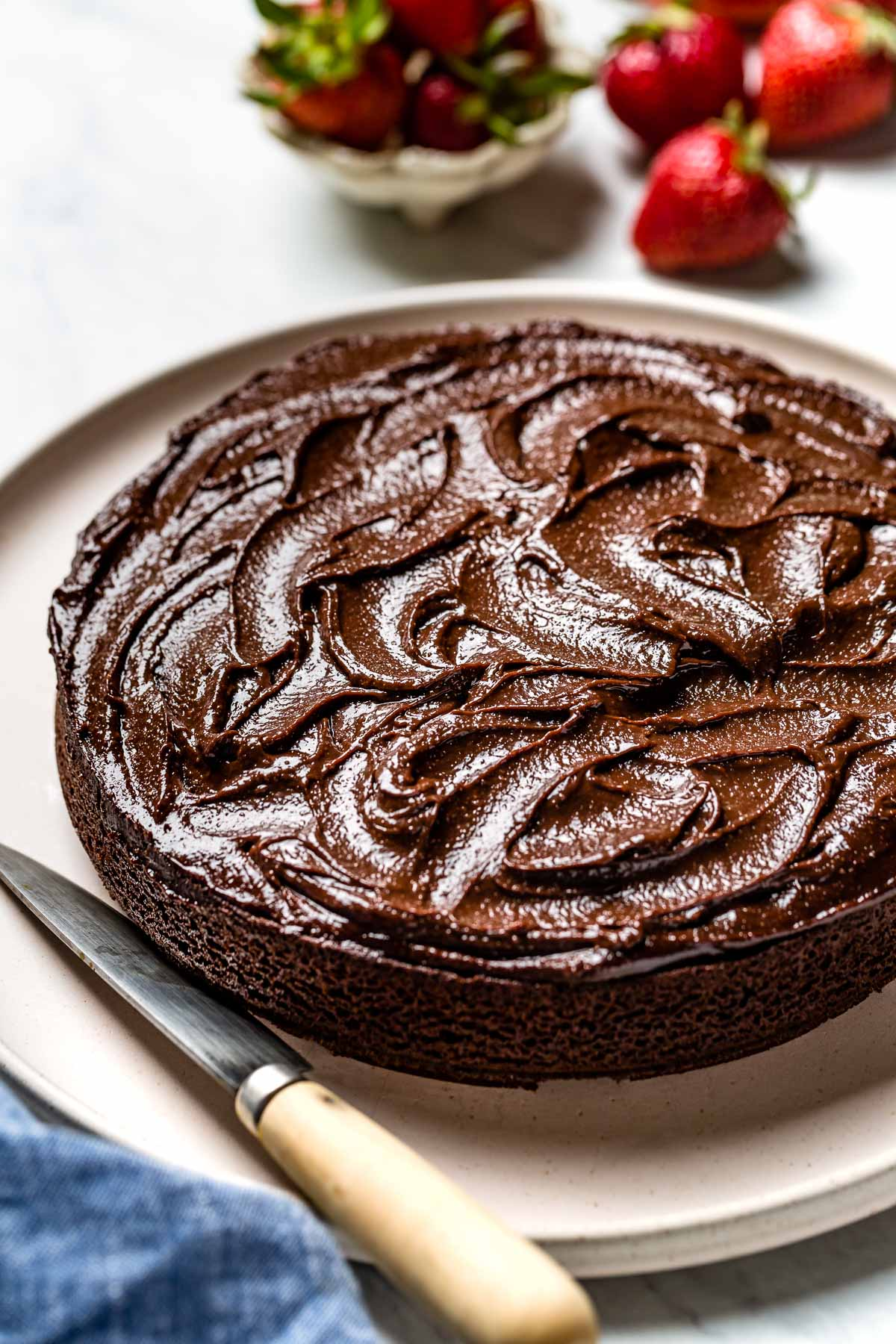 Almond flour chocolate cake spread with chocolate frosting with a knife on the side