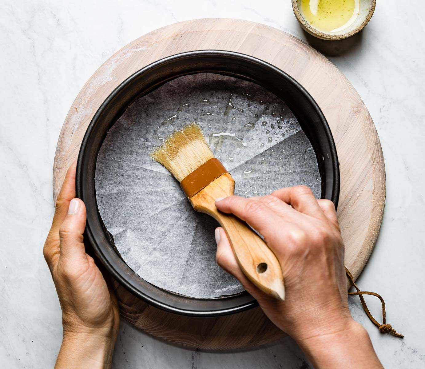 person greasing pan with oil