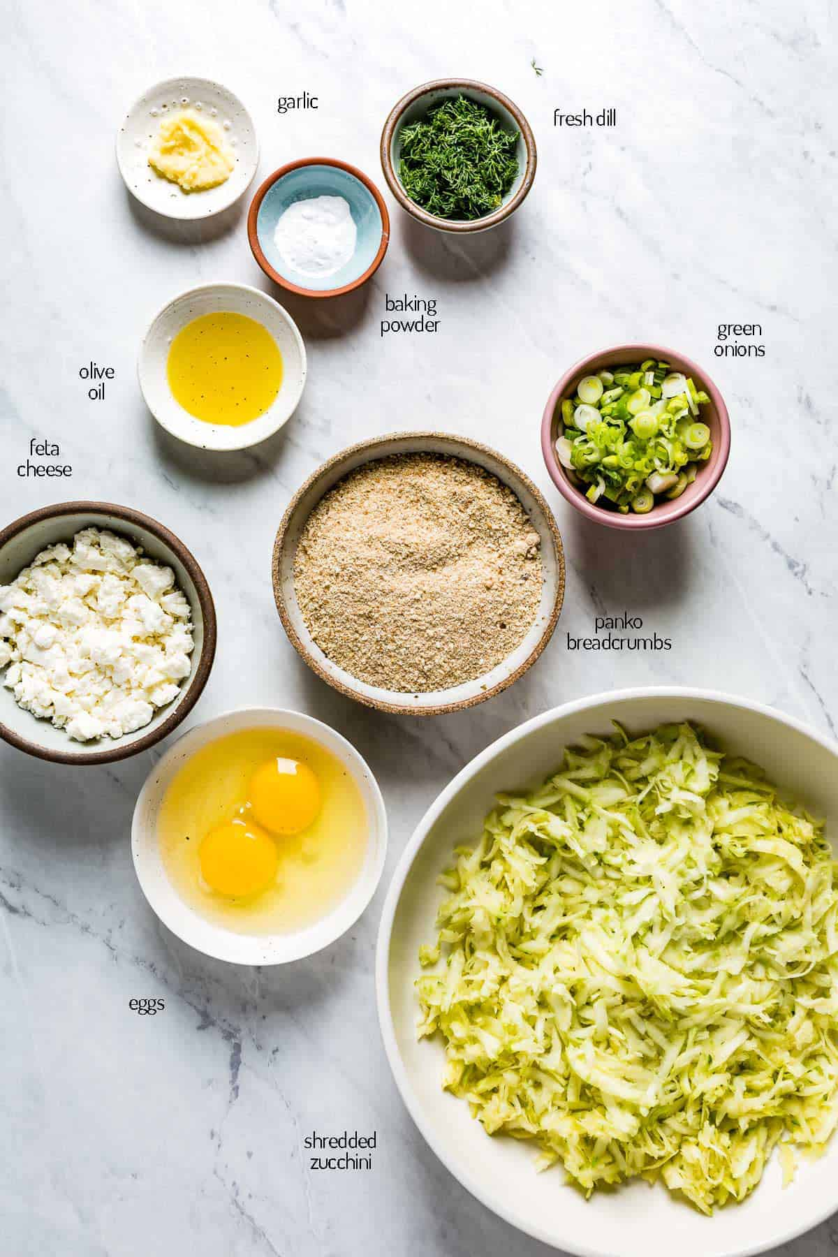 Ingredients for the recipes are placed in individual cups on a marble backdrop