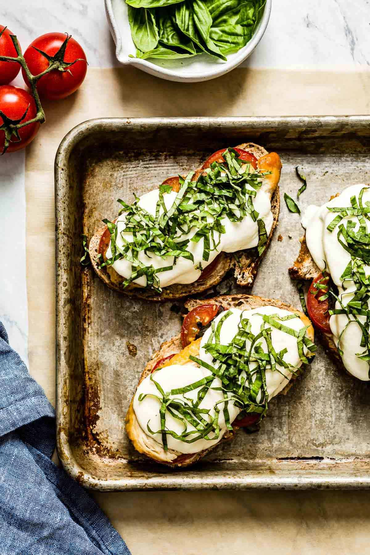 Three grilled chicken caprese sandwiches topped off with basil in a sheet pan
