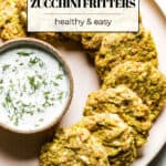 Zucchini fritters placed on a plate with yogurt sauce on the side with text on the image