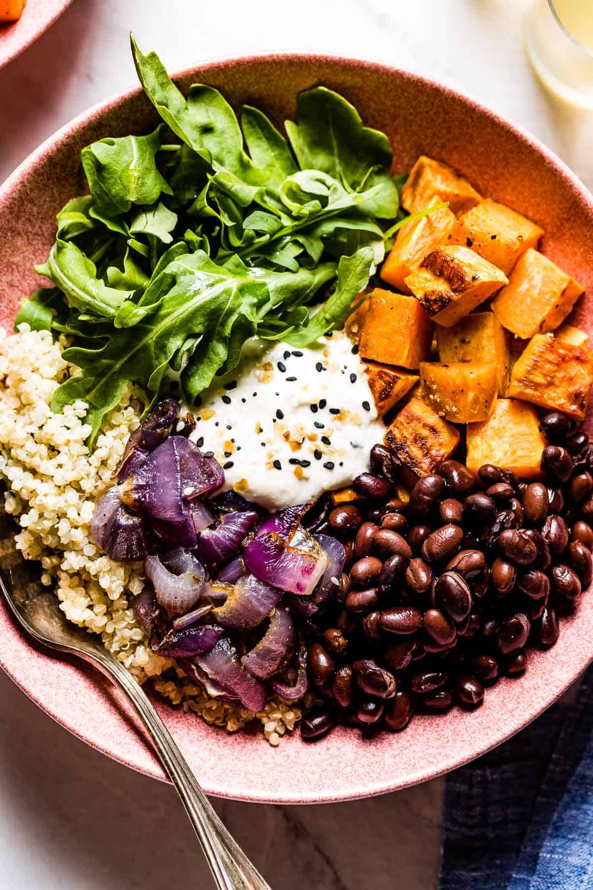A bowl of sweet potatoes, quinoa, and black beans garnished with tahini yogurt dressing with a spoon on the side.