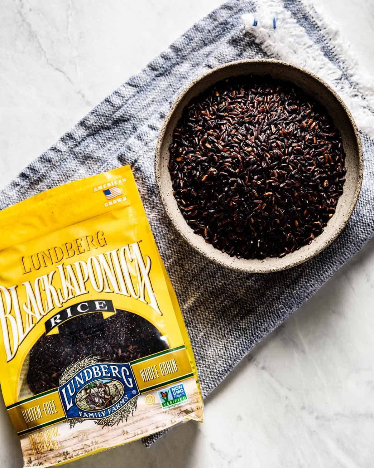 Black Japonica rice in its packaging with a bowl of it on the side