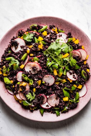 Black rice salad on a pink plate from the top view