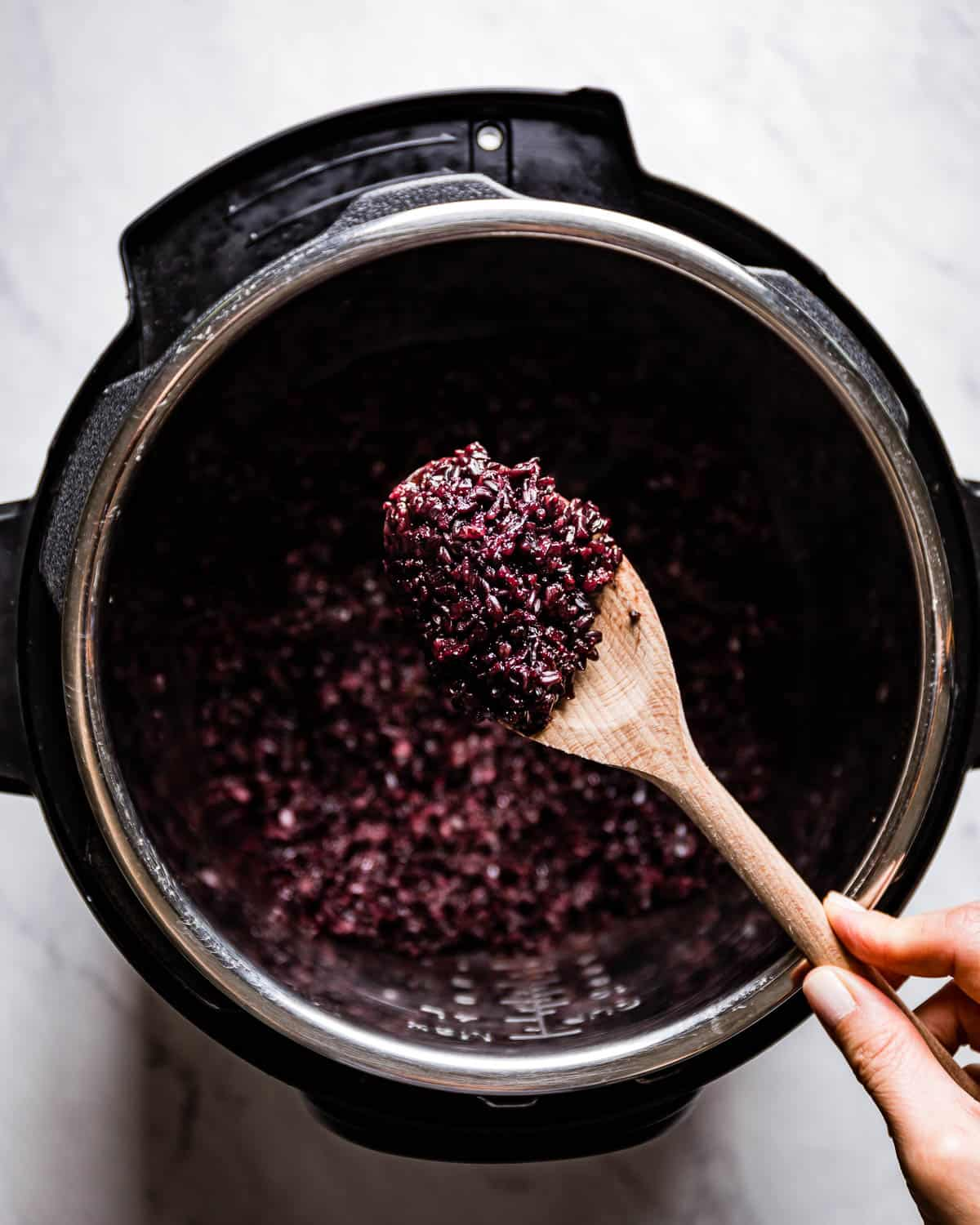 Person showing cooked black glutinous rice on a wooden spoon over pressure cooker