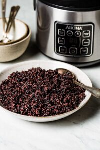 Black rice in a bowl with rice cooker in the backgroun