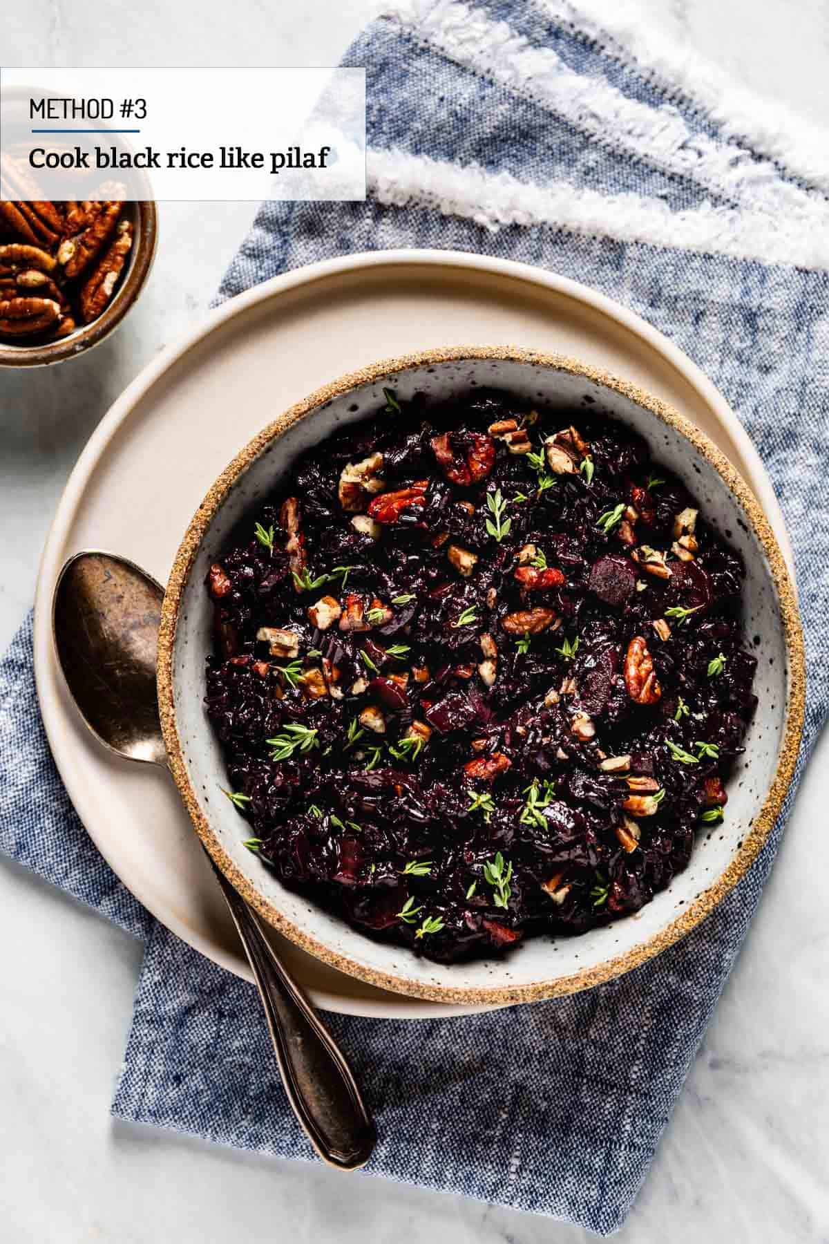 Black Rice pilaf in a bowl with a spoon on the side