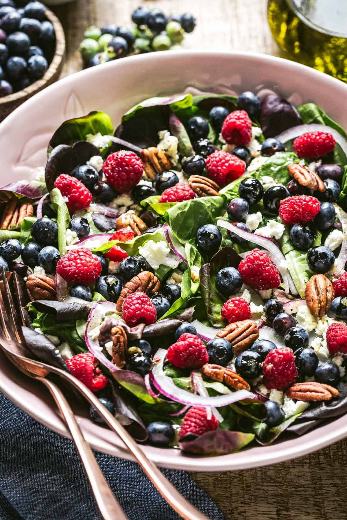 Spinach salad with blueberries and feta with spoons on the side