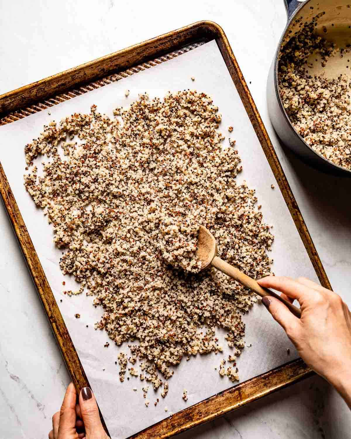 Person spreading quinoa on a baking sheet to cool off