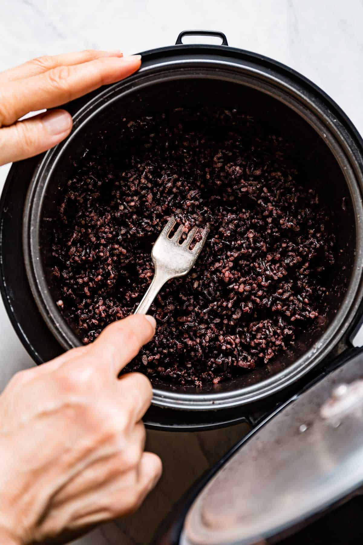 person fluffing cooked purple forbidden rice in a rice cooker