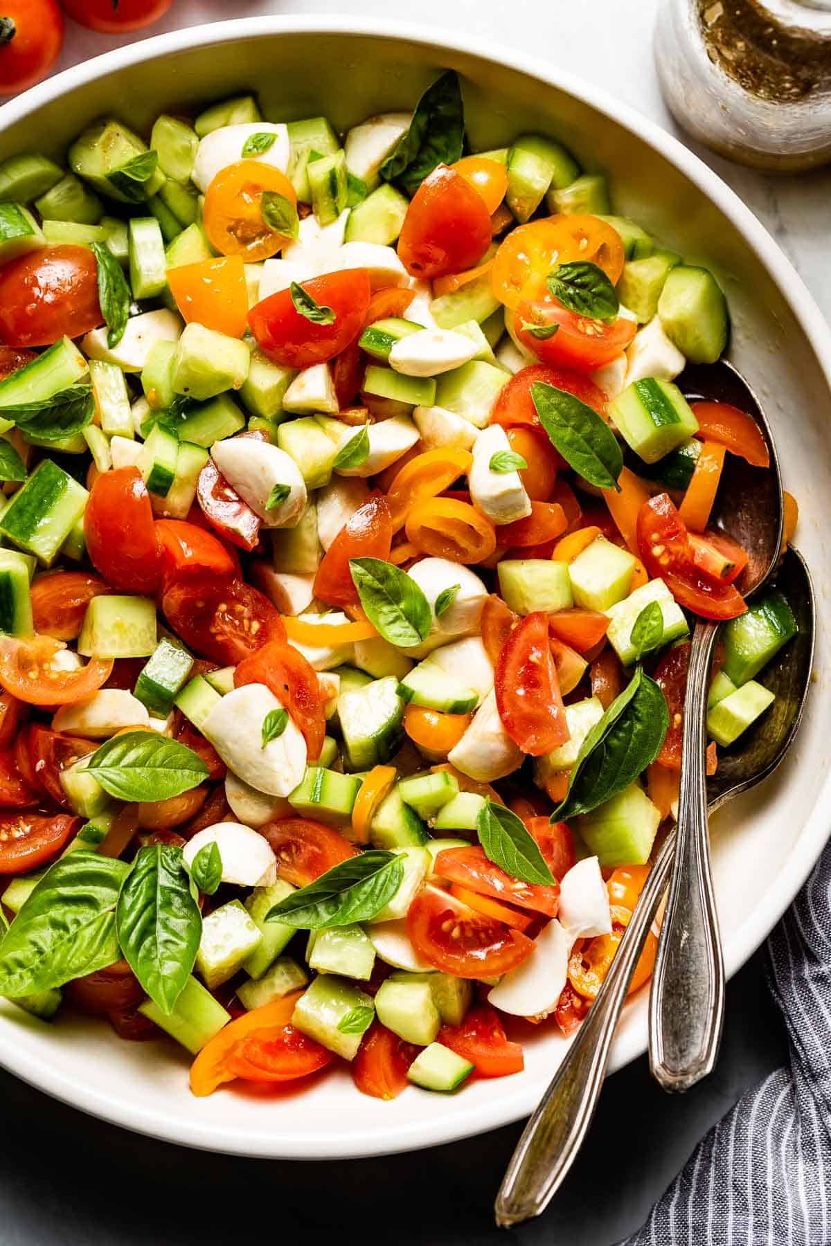 Cucumber Tomato Mozzarella Salad in a bowl with spoons on the side