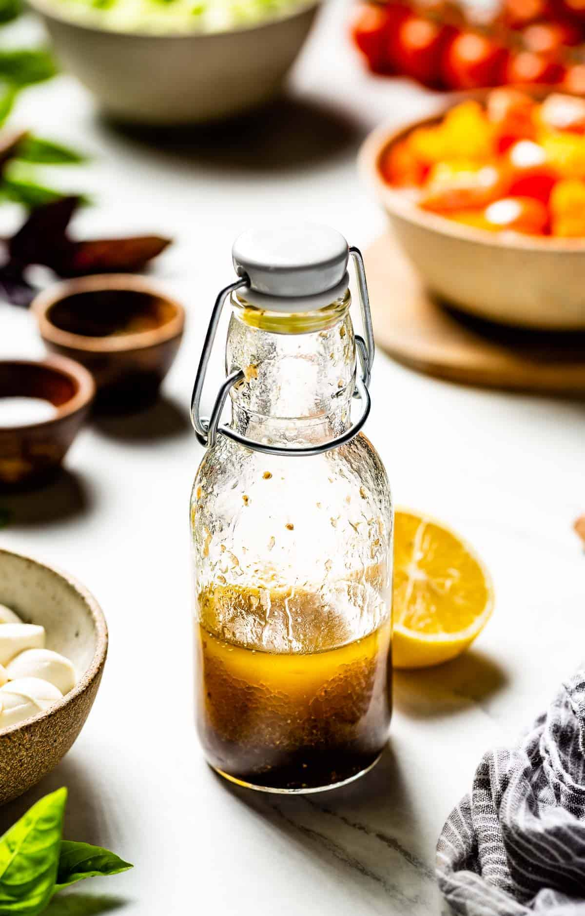 lemon balsamic vinaigrette placed in a bottle with salad ingredients around it.