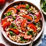 Piyaz - Turkish White Bean Salad in a bowl with a spoon on the side from top view.