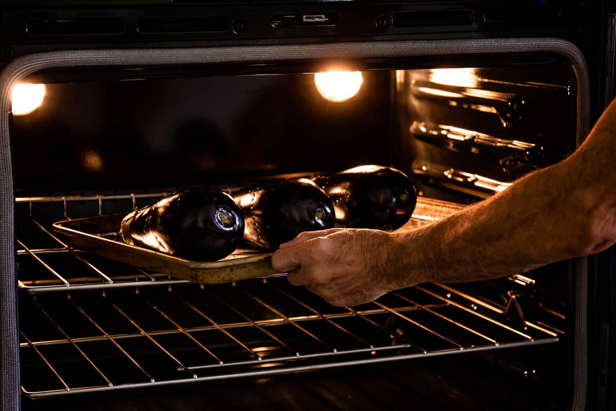 Person placing eggplants to roast in oven