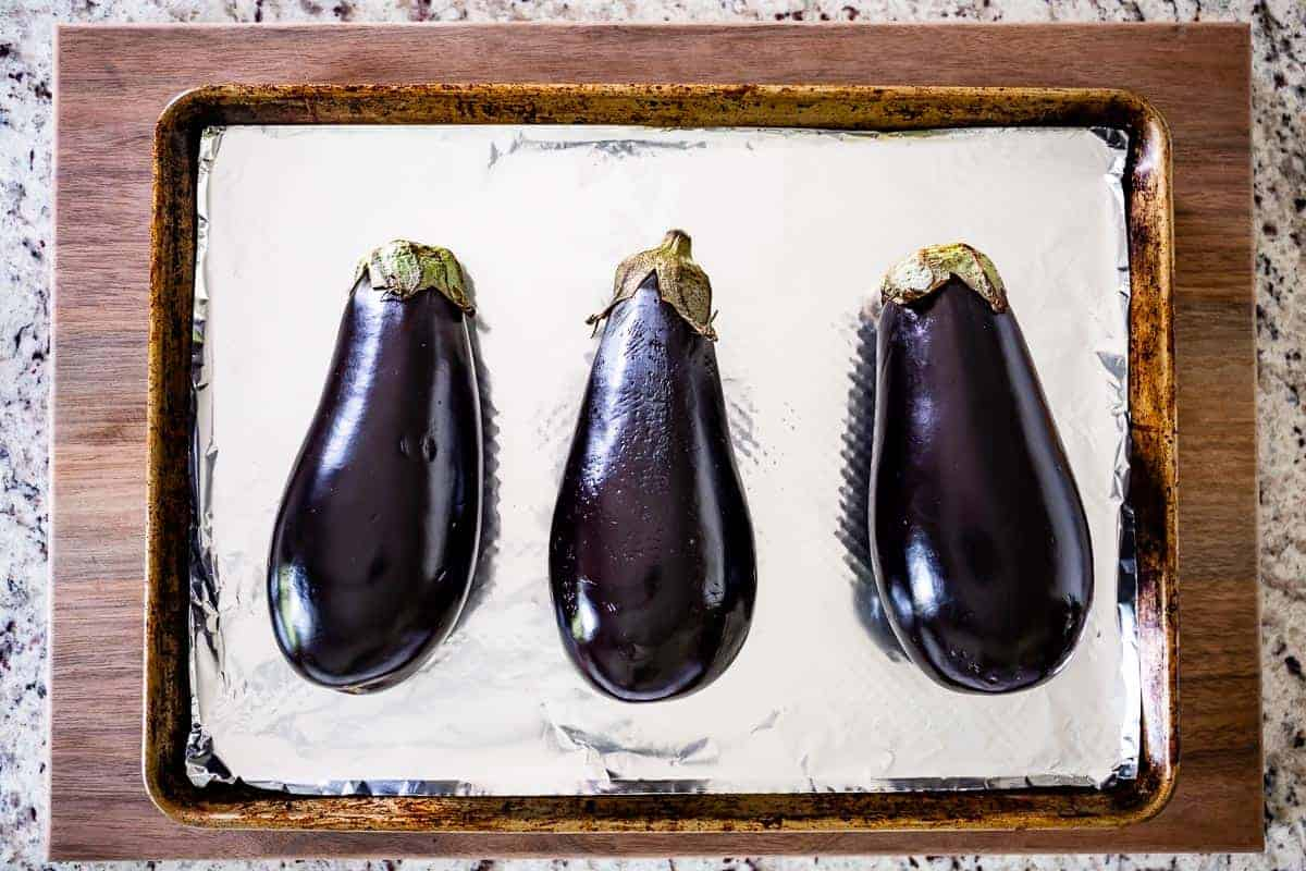 Globe eggplants on a sheet pan lined with aluminum foil