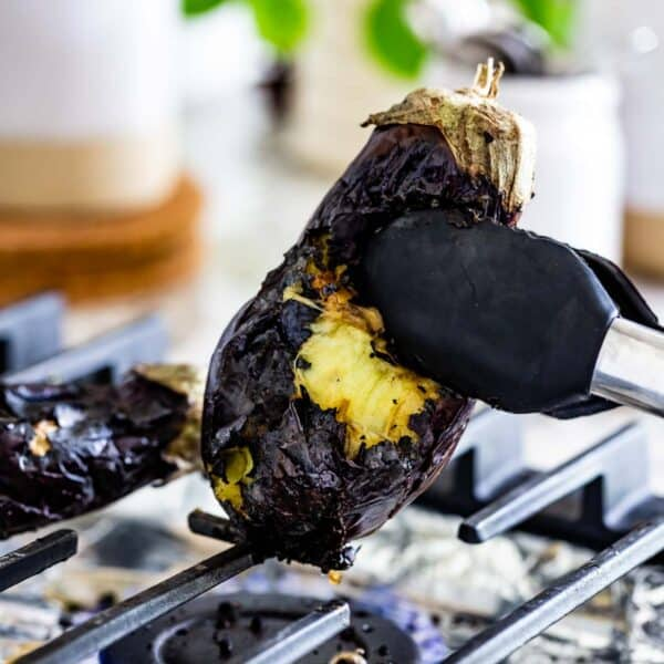 Person showing how to fire roast eggplant on a gas stove