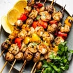 Grilled Shrimp Kabobs with Vegetables on a plate with herbs on the side