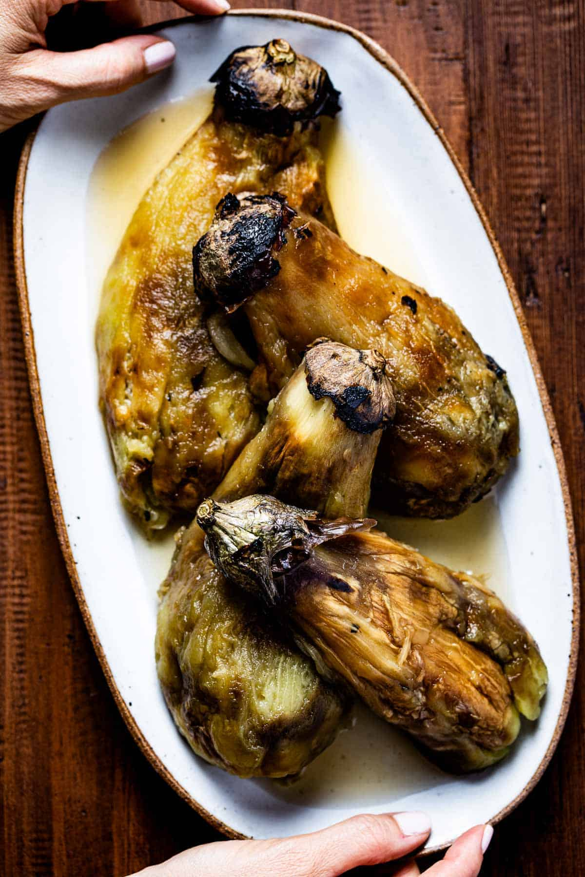 Fire roasted eggplants on a plate served by a person