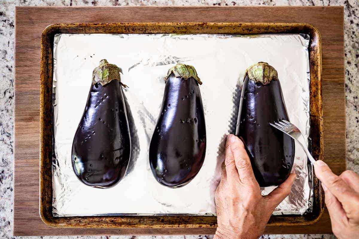 Person poking holes in an eggplant on a baking sheet