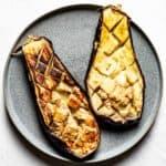 Halved roasted eggplants on a plate