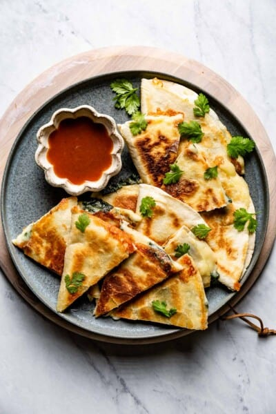 Spinach Quesadilla cut into small pieces served with sauce on the side