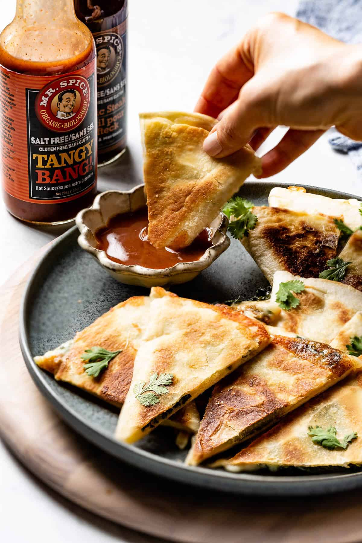 Person dipping spinach quesadillas in a sauce