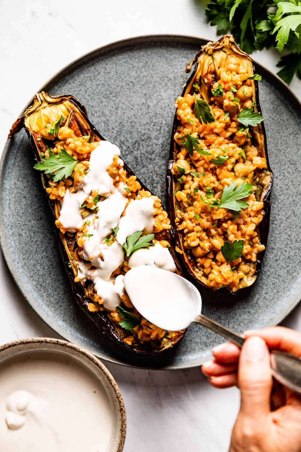 Baked stuffed eggplant is being drizzled with tahini sauce