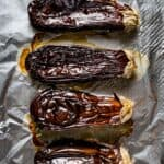 Whole roasted Eggplant on a sheet pan right after it comes out of the oven
