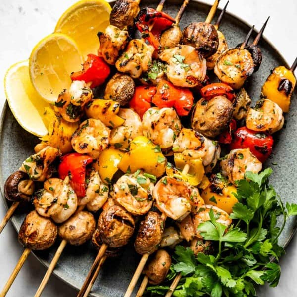 Grilled Shrimp Kabobs with Vegetables on a plate with wedges of lemon