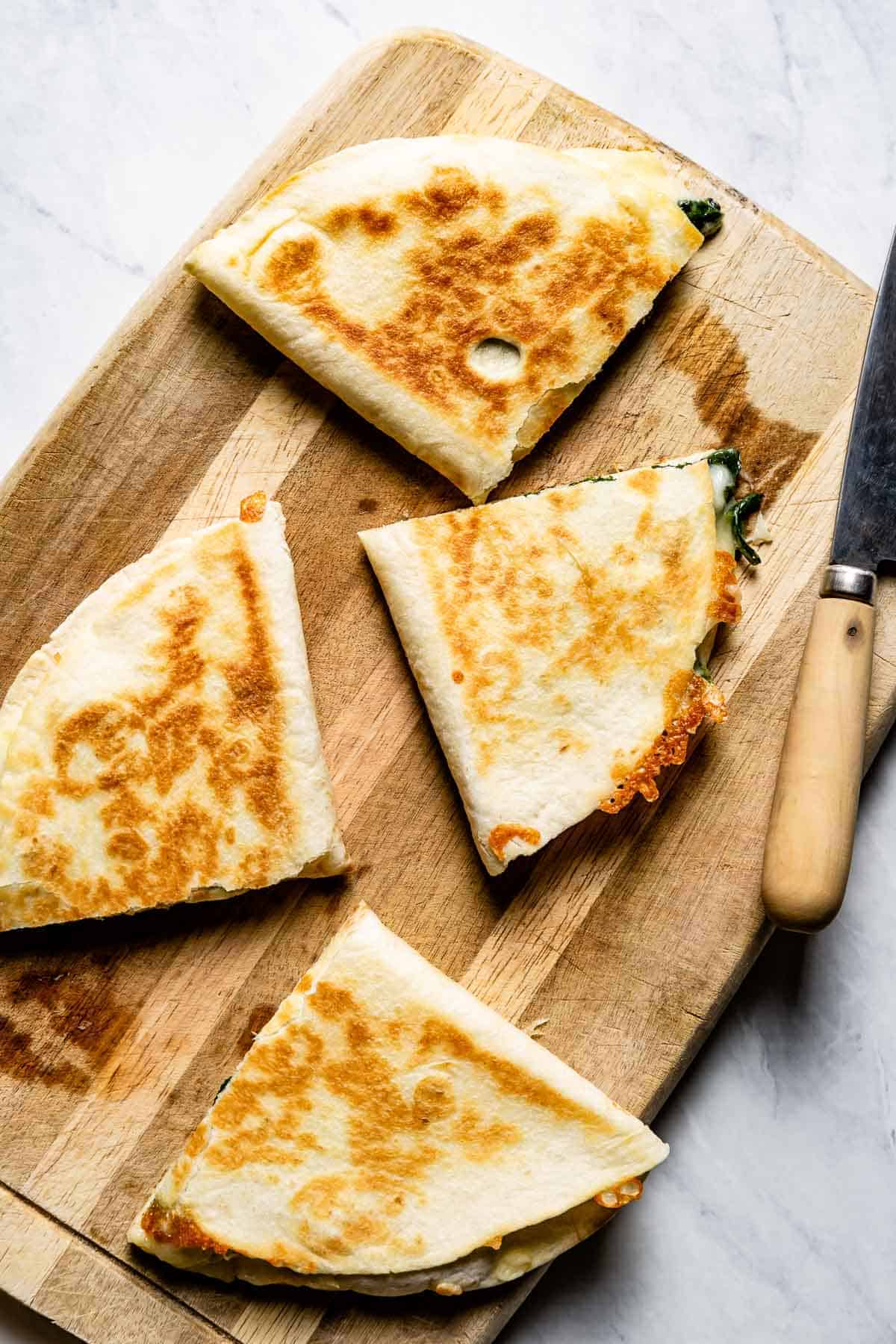 spinach cheese quesadilla cut into small pieces on a cutting board