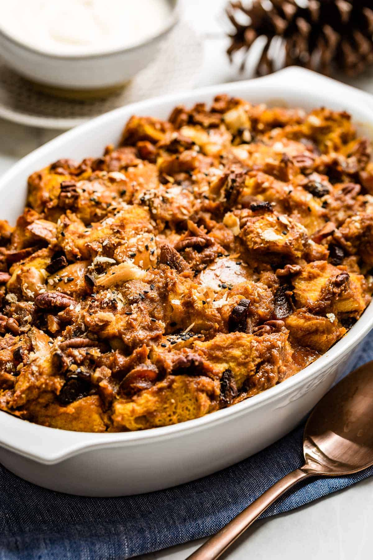 Pumpkin Challah Bread pudding freshly baked in a casserole dish a portion taken out with a bowl of creme fraiche on the side