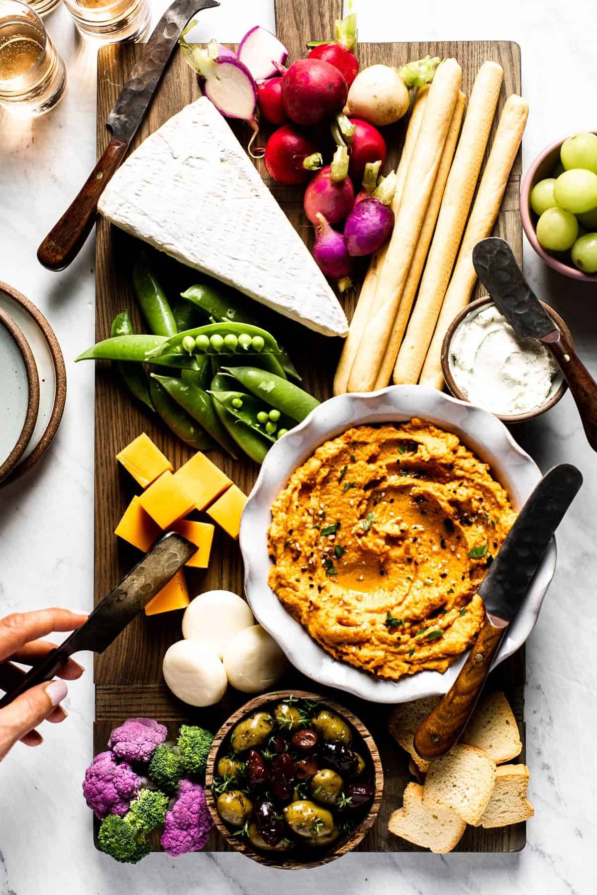 Carrot hummus is being served as a part of cheese platter