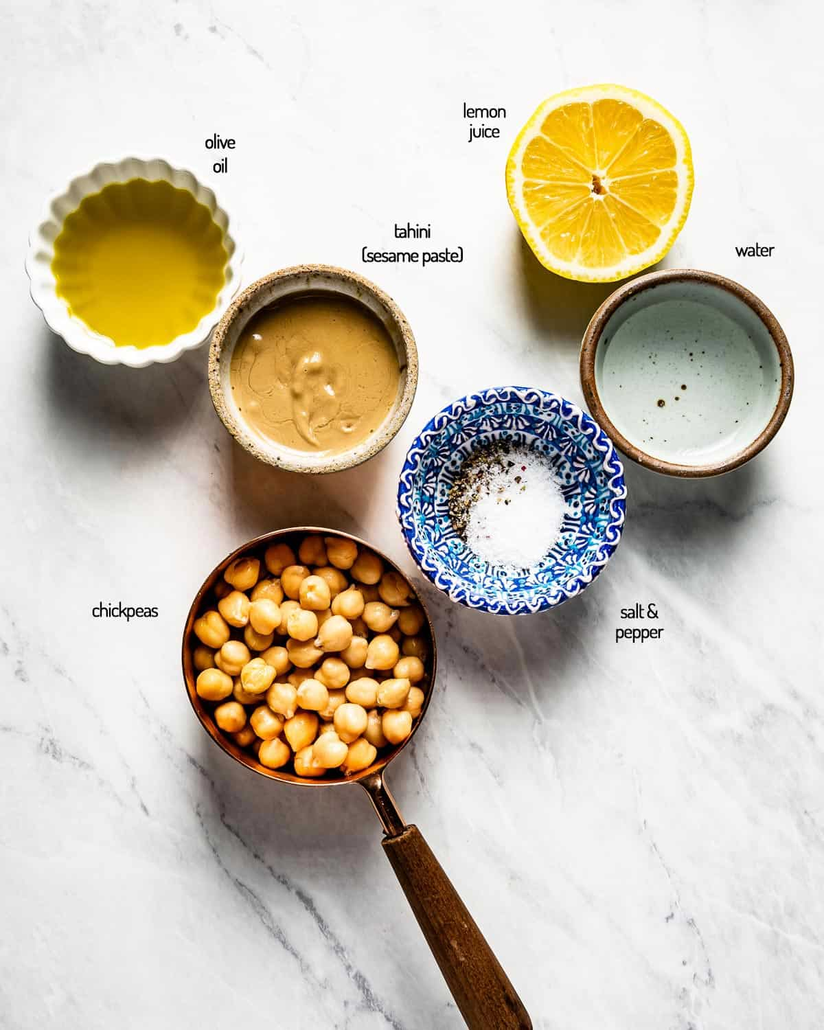 Regular hummus ingredients are portioned out and placed on a marble backdrop